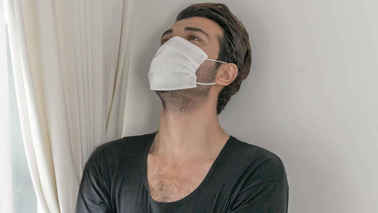 Homem usando máscara com o rosto inclinado para cima com expressão de incerteza