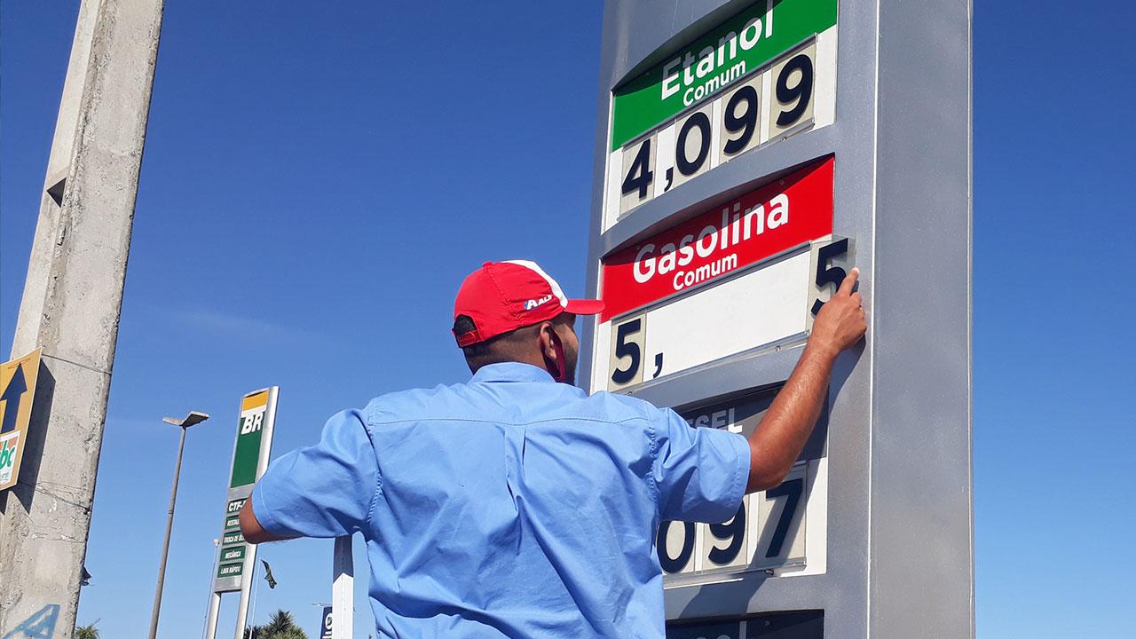 Funcionário de posto atualizando preço dos combustíveis